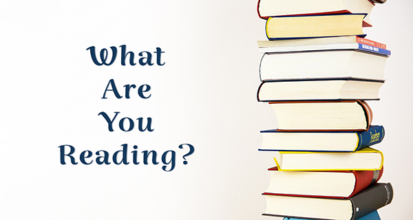 The words What Are You Reading are shown on a blank white background with a stack of books to the right of it