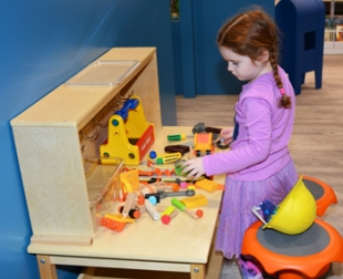 A girl plays at the tool bench station