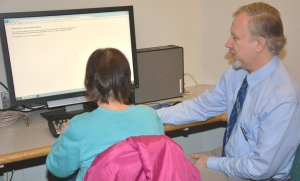 Photo: OCPL staff assisting patron with screen reader