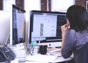 photo - woman looking at a computer screen